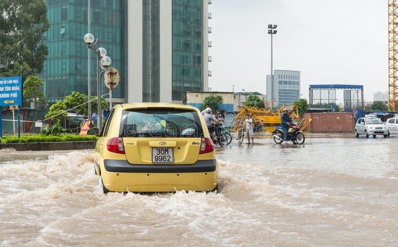 Taxi que lucha a través de la inundación