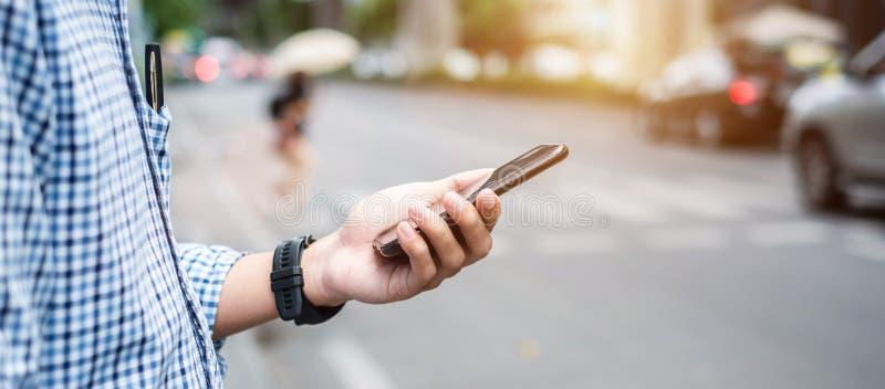 Taxi que ordena del hombre de negocios turístico o casual del hombre joven vía el uso del taxi en smartphone en la calle de la ci fotografía de archivo
