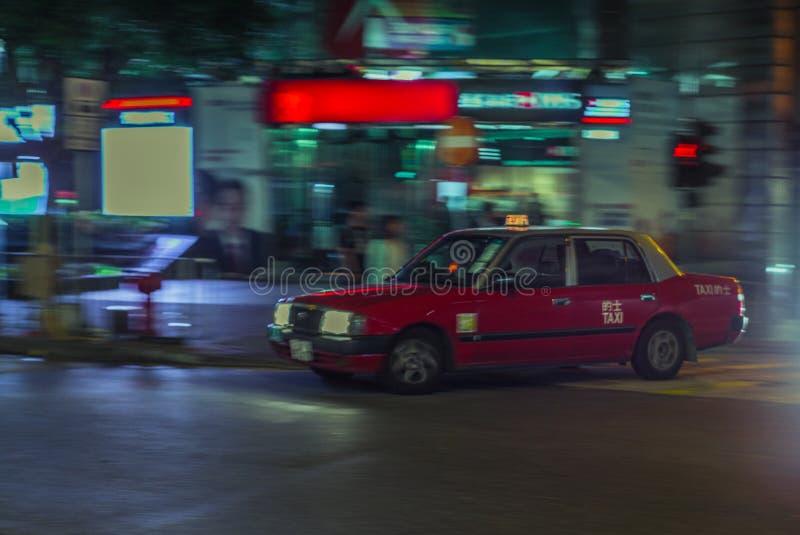 Taxi rojo que acomete en el más streest de Hong Kong en la noche con moti fotografía de archivo libre de regalías