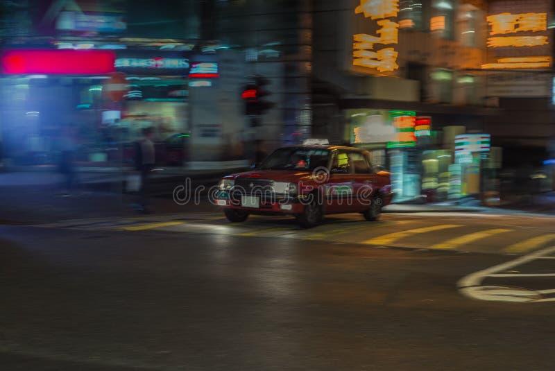 Taxi rojo que acomete en el más streest de Hong Kong en la noche con moti fotos de archivo libres de regalías