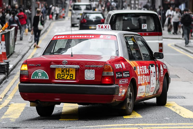 Taxi rojo y blanco de los colores, símbolo de HK, cerca del cuadrado de Lan Kwai Fong de calles en distrito central Señal y desti fotos de archivo