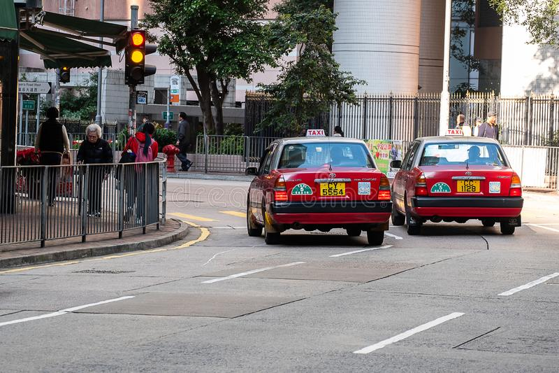 Taxi rosso e bianco di colori, simbolo della HK, sulla strada di Hollywood vicino al distretto pallido di Sheung e della centrale immagini stock