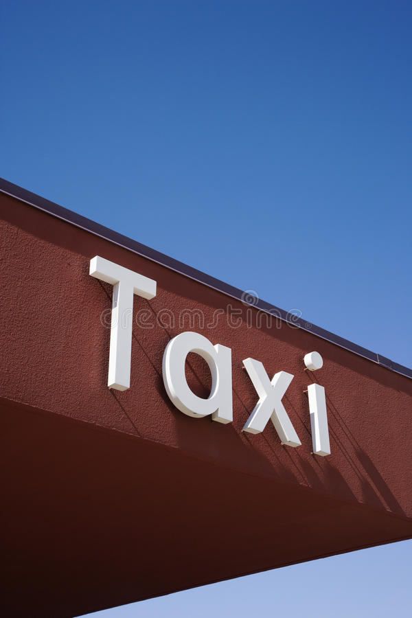 Taxi Sign On A Brown Wall Royalty Free Stock Image