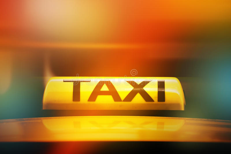 Taxi Sign on Car Rooftop, Street Light Bokeh stock images