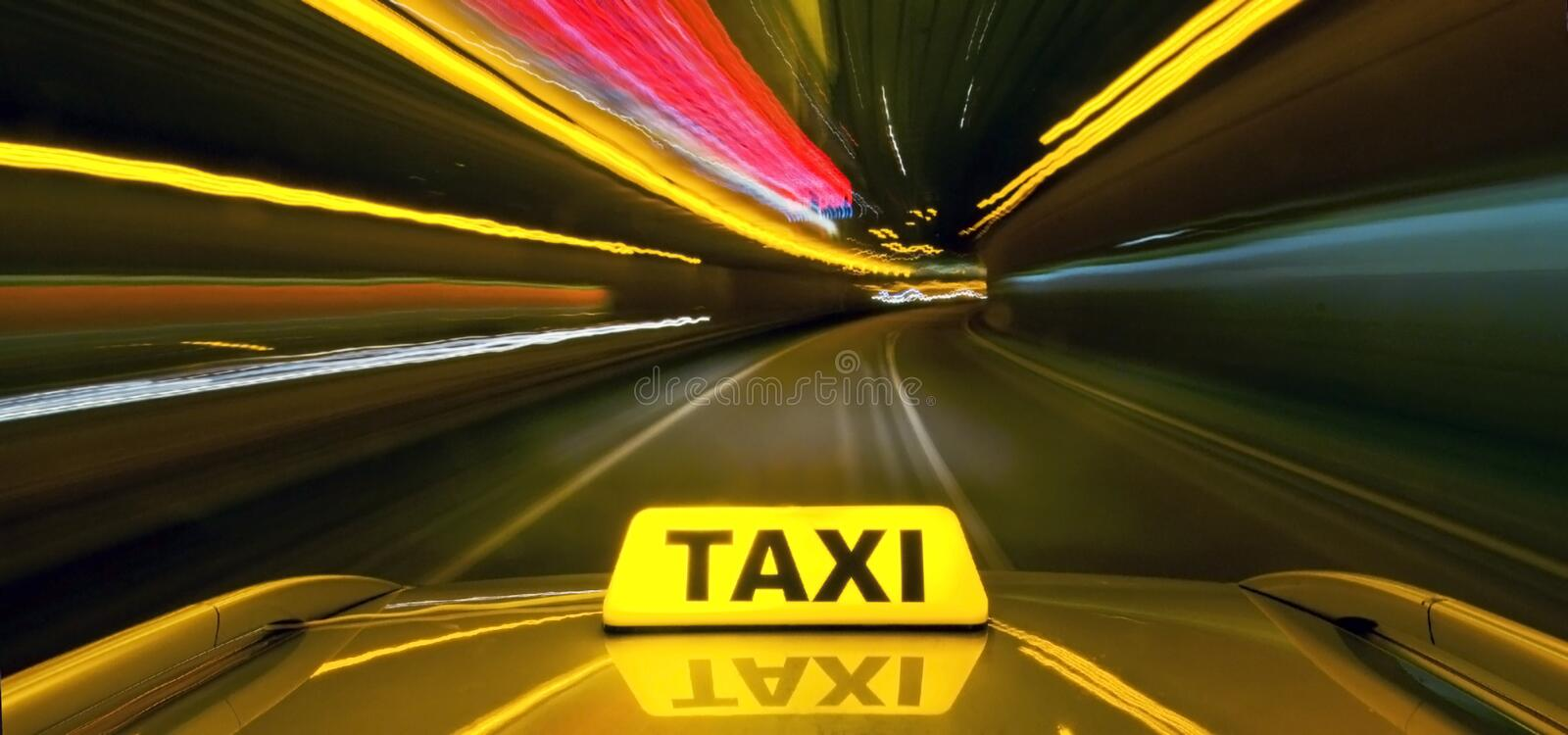 Taxi at warp speed. Taxi driving at high speed through the heavy traffic at night, seen from the roof of the cab