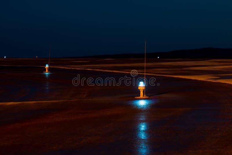 Taxibaan, zijrijlichten bij de nachtluchthaven stock foto