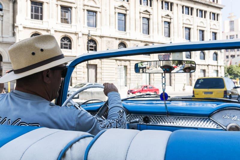 Taxibestuurder in Cuba die blauw Chevy Belair drijven stock afbeeldingen