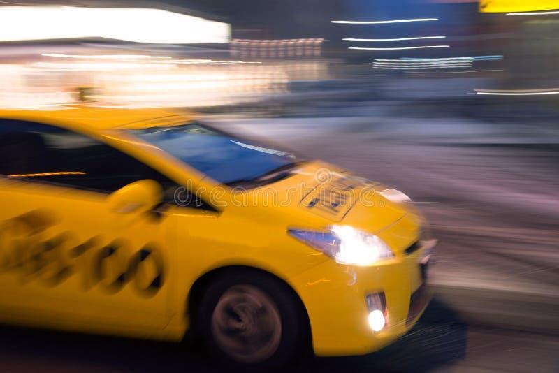 Taxibilflyttning som är snabb i nattstaden i rörelsesuddighet royaltyfri bild