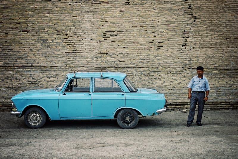 Taxichaufför bredvid hans klassiska sovjetiska bil i den historiska walled staden av den siden- vägen arkivfoton