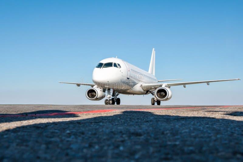 Taxiing um avião branco do passageiro no avental do aeroporto fotos de stock