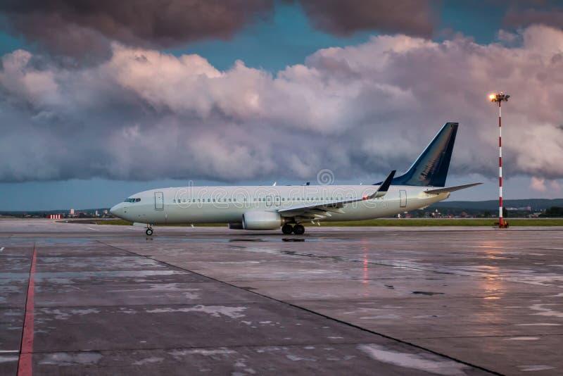 Taxiing um avião de passageiro no avental do aeroporto em uma noite nublado após a chuva fotografia de stock royalty free