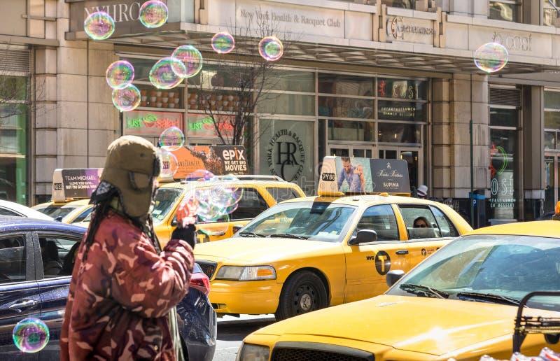 Taxis amarillos y vendedor sin hogar en New York City imagen de archivo libre de regalías