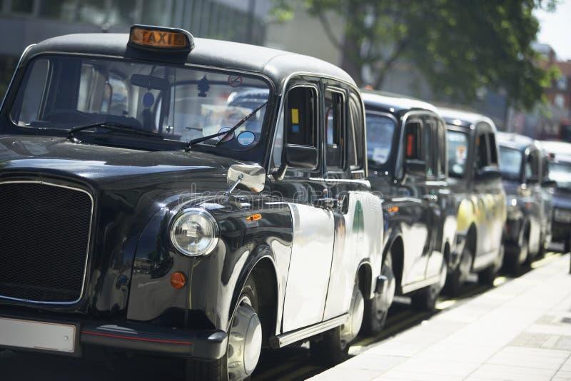 Taxis de Londres alineados en la acera foto de archivo