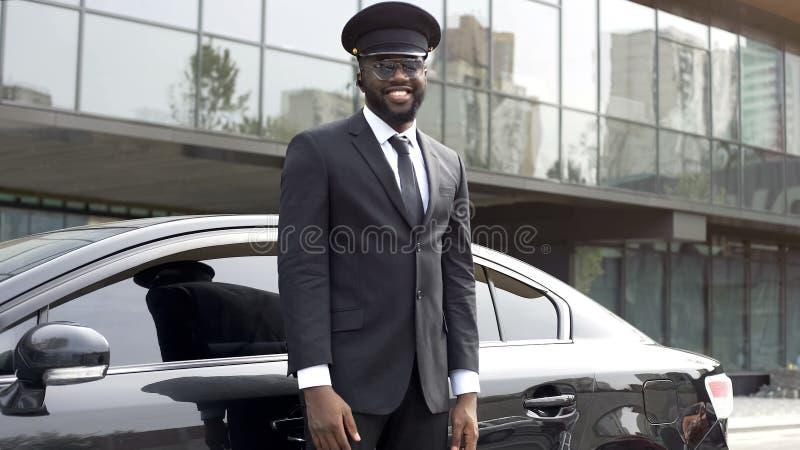Taxista hermoso que sonríe sinceramente cerca de su vehículo de lujo, servicio de la élite fotografía de archivo libre de regalías