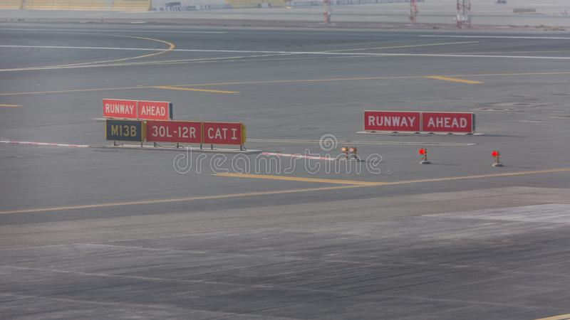 Sign markings on taxiway for direction at airport. Taxiway light in front of airfield runway signage, airport details for pilots royalty free stock photo
