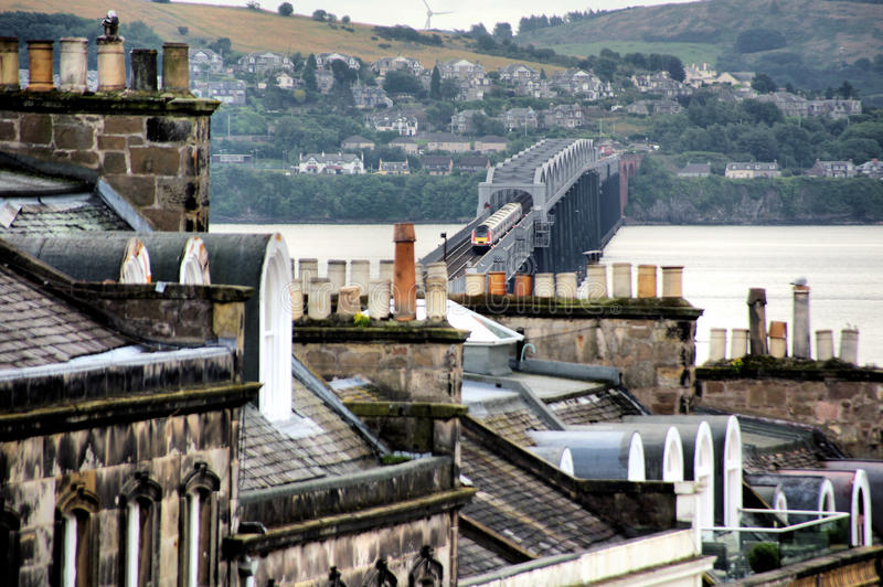 Tay Railway Bridge from Dundee. A train crossing the Tay Railway Bridge from Newport on Tay as viewed over the old slate rooftops of the City of Dundee in stock images