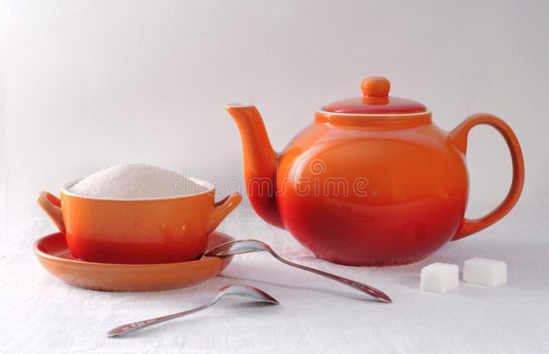 Tazón de fuente anaranjado de la tetera y de azúcar en un fondo blanco imagen de archivo