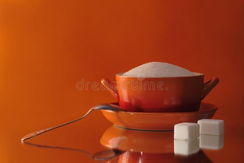 Tazón de fuente de azúcar con una cucharilla en un fondo anaranjado imagenes de archivo