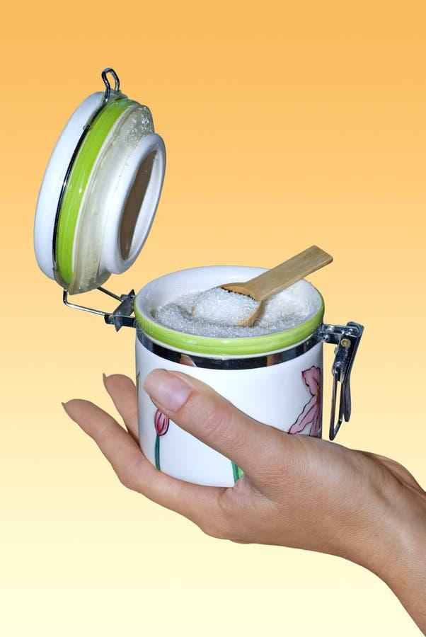 Tazón de fuente de azúcar en la mano con el camino fotos de archivo