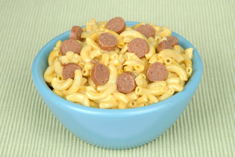Tazón de fuente de macarrones y de queso con las rebanadas del perrito caliente foto de archivo libre de regalías