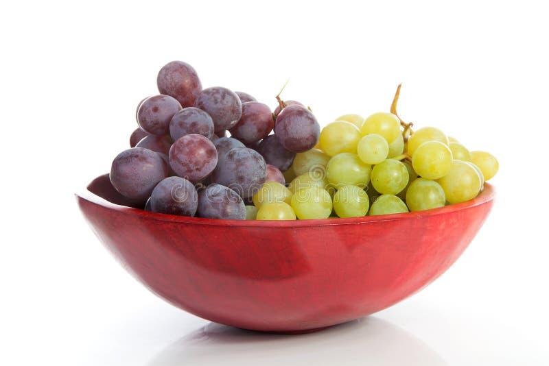 Tazón de fuente rojo con las uvas imagenes de archivo