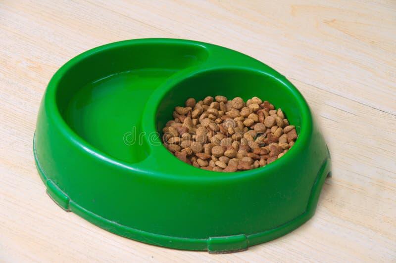 Tazón de fuente verde del animal doméstico con las galletas imagen de archivo