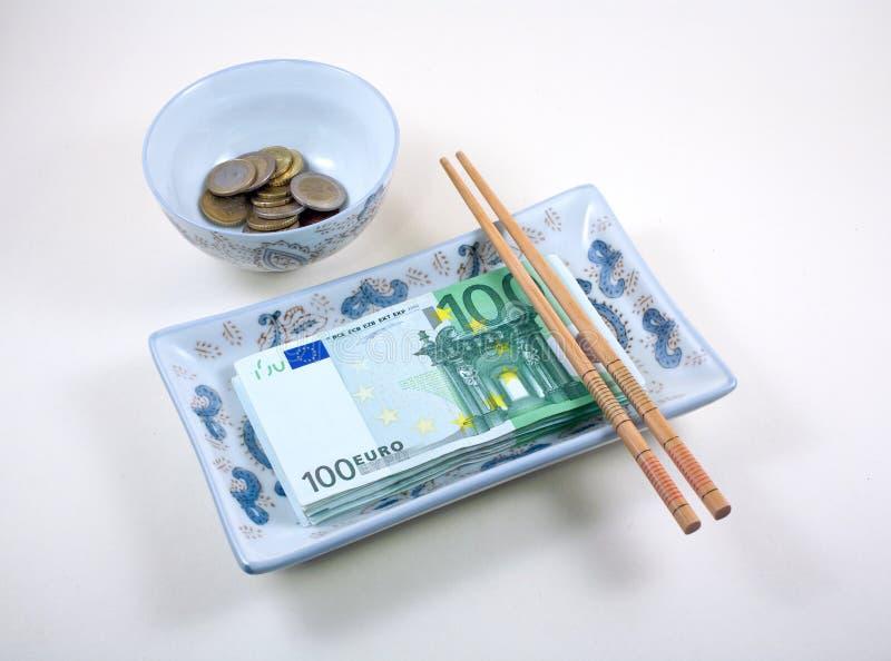 Tazón de fuente y plato por completo de euros con los palillos imagen de archivo