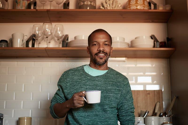 Taza afroamericana de la tenencia del hombre negro de café en casa fotografía de archivo libre de regalías