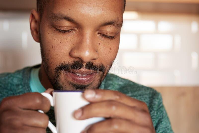 Taza afroamericana de la tenencia del hombre negro de café en casa primer fotos de archivo libres de regalías