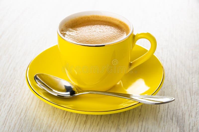 Taza amarilla con el café, cuchara en el platillo en la tabla de madera fotografía de archivo