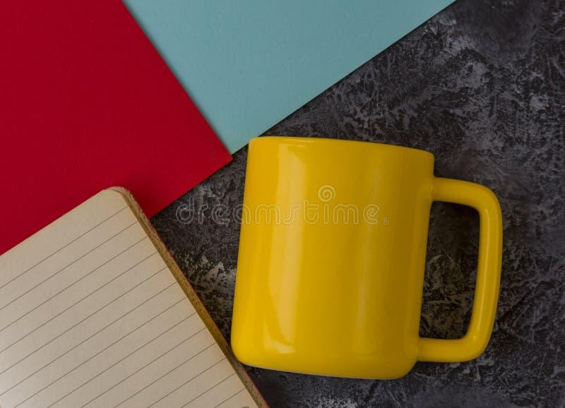 Taza amarilla con el cuaderno en fondo de piedra oscuro Papel azul y rojo Con el espacio de la copia imagen de archivo libre de regalías
