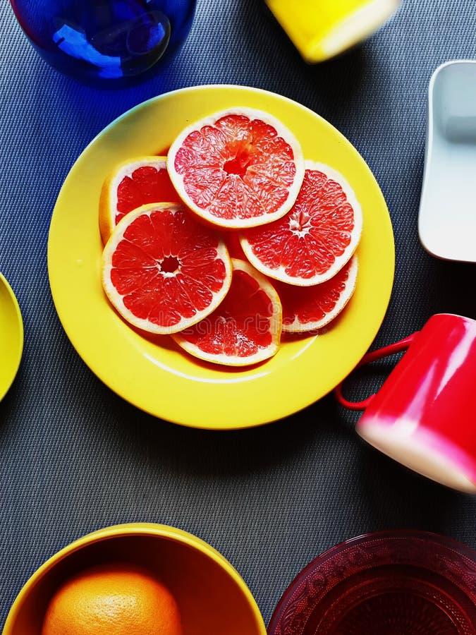 Taza amarilla de los platos de la taza de la placa amarilla azul roja colorida brillante del florero en todavía del fondo illu ro imágenes de archivo libres de regalías