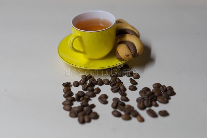 Taza amarilla de t?, de granos de caf? y de galletas imagen de archivo