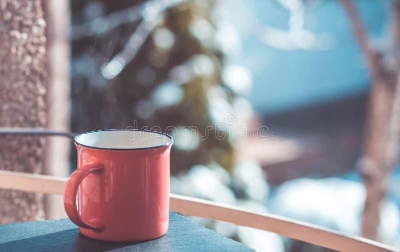 Taza anaranjada de té en la ventana, congelada imagen de archivo