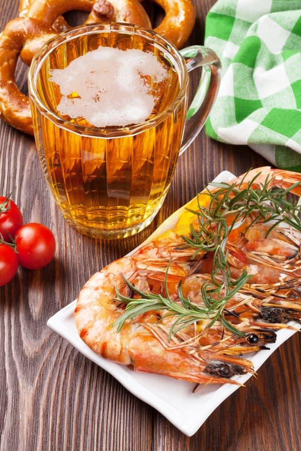 Taza asada a la parrilla de los camarones, del pretzel y de cerveza imagen de archivo
