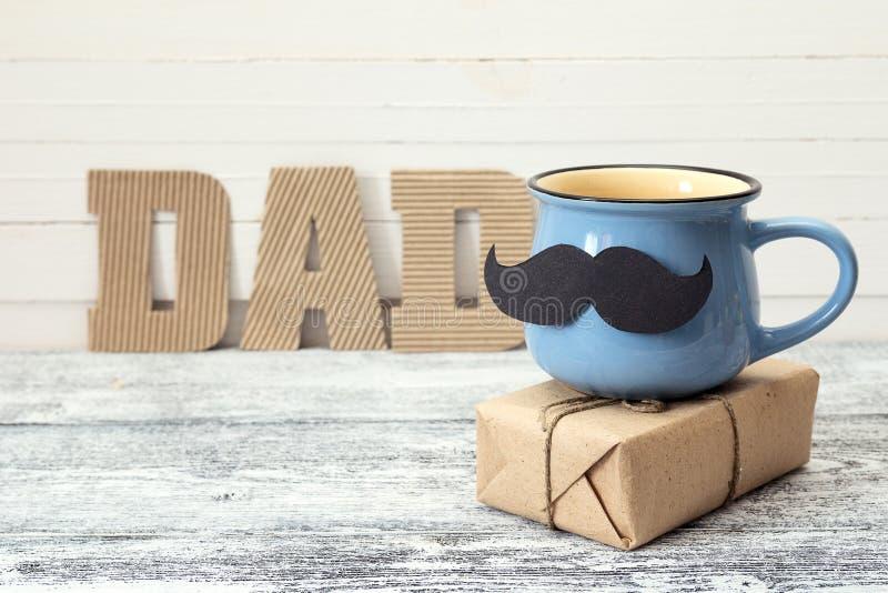 Taza azul con un bigote, la caja de regalo y un papá de la inscripción en imágenes de archivo libres de regalías