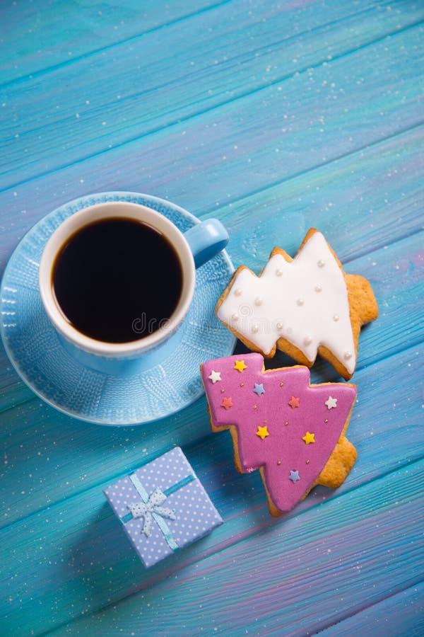 Taza azul de café caliente con la galleta festiva esmaltada de la Navidad en la forma de abeto en fondo de madera azul fotos de archivo libres de regalías