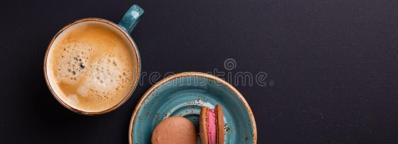 Taza azul de café y de macarrones en la tabla de madera oscura Rotura de Coffe foto de archivo libre de regalías