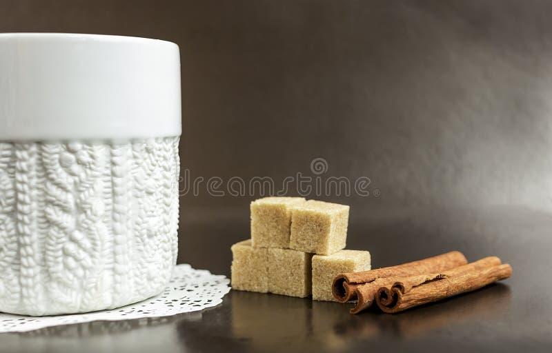 Taza blanca con café en un fondo oscuro con el azúcar foto de archivo