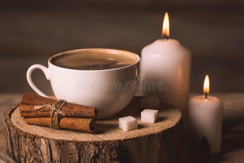 Taza blanca con café, las velas, el azúcar y el canela fotos de archivo