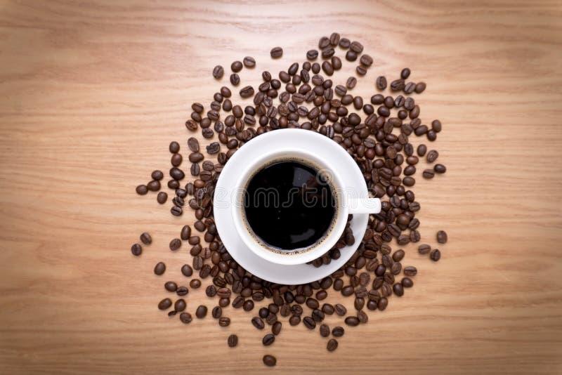 Taza blanca con el café negro, caliente que se coloca en habas marrones, asadas en la tabla de madera imágenes de archivo libres de regalías