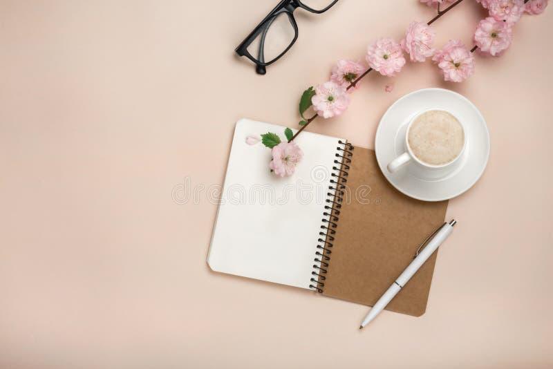 Taza blanca con el capuchino, flores de Sakura, cuaderno en un fondo rosado en colores pastel fotos de archivo libres de regalías