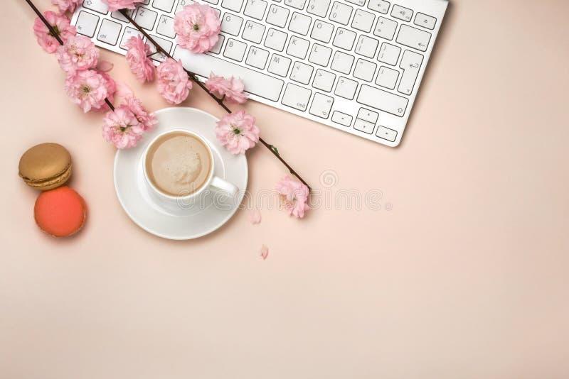 Taza blanca con el capuchino, flores de Sakura, teclado en un fondo rosado en colores pastel imagenes de archivo