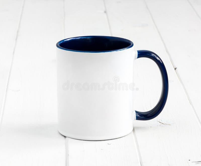 Taza blanca con el interior azul marino en una tabla imagenes de archivo