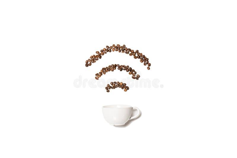 Taza blanca con los granos de café en la forma del símbolo del Wi-Fi imagenes de archivo