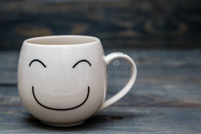Taza blanca con Smiley Face en la tabla de madera azul fotografía de archivo libre de regalías