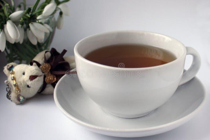 Taza blanca con té en un platillo blanco en una tabla de madera, un llavero un cachorro de oso y un ramo de snowdrops imagen de archivo