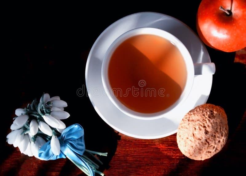 Taza blanca con té en un platillo con las galletas de harina de avena y la manzana roja y un pequeño ramo de snowdrops atados con fotos de archivo libres de regalías