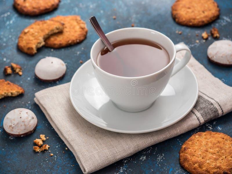 Taza blanca con té negro y galletas en fondo azul Todavía de la comida vida hermosa fotografía de archivo libre de regalías