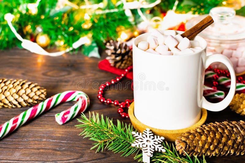 Taza blanca de cacao con las melcochas, las piruletas, los conos de abeto, la rama de árbol de navidad, la guirnalda y el copo de foto de archivo